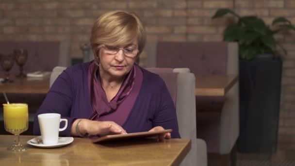 eine Frau mittleren Alters in einem Café, die erstaunt auf das Tablet blickt. sie hält inne, blättert, drückt negative Emotionen aus