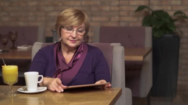 eine ziemlich reife Frau in einem Café, die lächelnd auf den Tablet-Bildschirm blickt. sie blättert und lacht ein bisschen glücklich