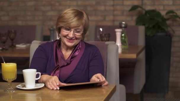 Ein Porträt von einer schönen Frau mittleren Alters in einem Café mit Blick auf das Tablett und lachen. Sie scrollt der Bildschirm