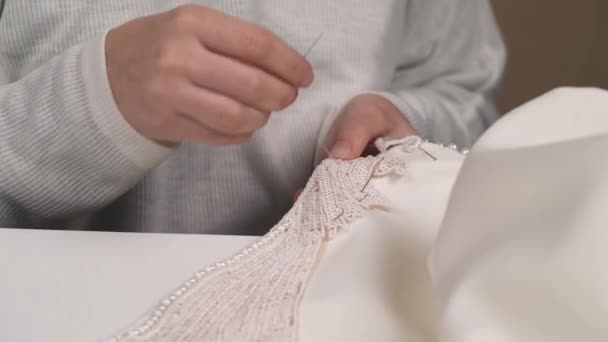 A front view of womans hands stitching beaded lace down the wedding dress