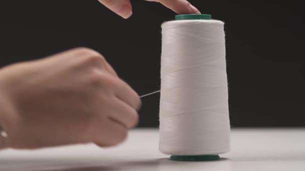eine Nahaufnahme einer Spule mit weißem Faden; eine Hand beginnt, den Faden abzuwickeln und mit einer Schere abzuschneiden