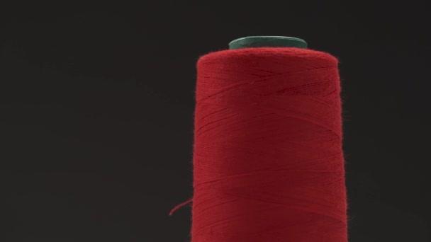 Eine Nahaufnahme der Spule mit rotem Faden und einer Hand, die sie nach oben hält, beginnt, den Faden abzuwickeln; dann schneidet man ihn mit der Schere ab