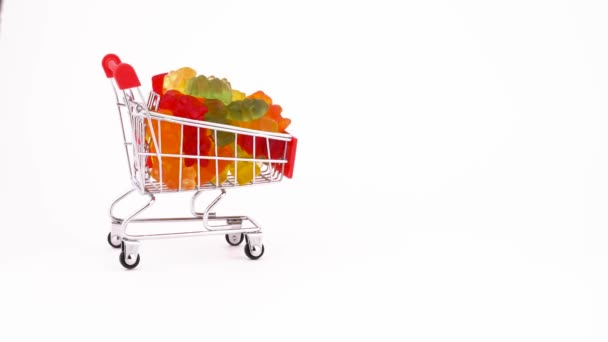 Shopping cart with bear shaped sweet gummy candies is moving forward. Isolated on the white background. Close-up. Macro.
