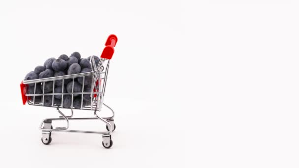 Half frame of shopping cart with fresh blueberries rotating on the turntable. Isolated on the white background. Close-up. Macro.