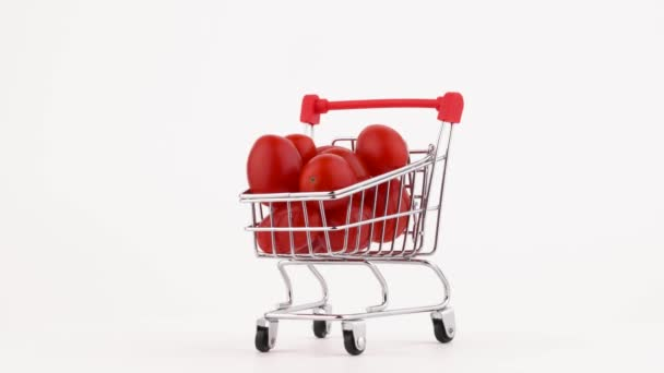 Supermarket trolley packed with red cherry tomatoes pile. Rotating on the turntable. Isolated on the white background. Close-up. Macro.