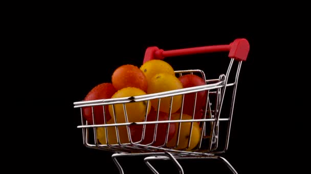 Macro shooting of shopping cart packed with red and yellow grape tomatoes pile with water drops. Rotating on the turntable. Isolated on the black background. Close-up.