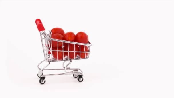 Moving supermarket trolley packed with red grape tomatoes pile with water drops. Isolated on the white background. Close-up. Macro.