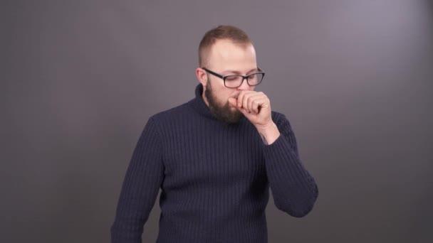Detail portrét kašle muž v brýlích s vousy. Izolované na šedém pozadí