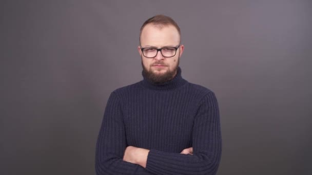 Portrét mladého muže s plnovousem a brýlemi. Při pohledu na fotoaparát s hněvem a mává rukama. Izolované na šedém pozadí