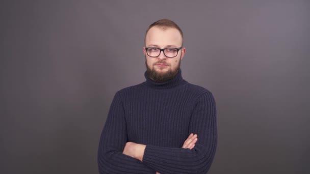 Portrét mladé vousatý muž v brýlích s překřížením rukou při pohledu na fotoaparát. Izolované na šedém pozadí.