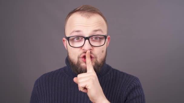 Detailní portrét vousatý kavkazské mladíka v brýle ukazuje být tiché znamení. Rty s prstem. Gesto mlčení. Izolované na šedém pozadí