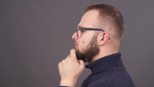 Extreme close-up male profile portrait, stroking his beard. Isolated on grey background.