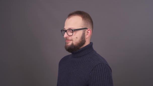 Detailní portrét profilu mladých vousy muž v brýlích. Neočekávaný ironické, směje se na kameru. Izolované na šedém pozadí.