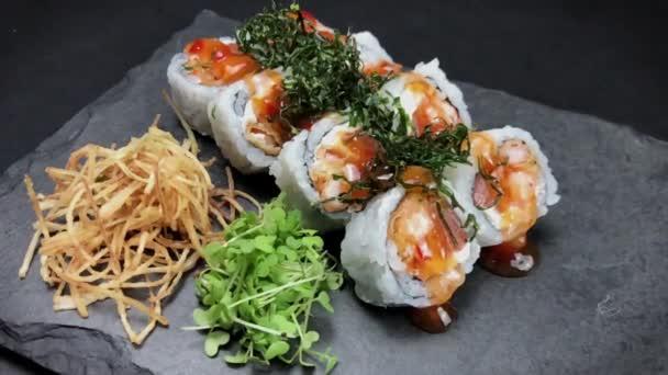 Sushi roll nastaven na černém břidlicovém pozadí. Různé Sushi Uramaki japonské jídlo v restauraci. . Japonská restaurace menu. 4K