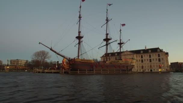 Tradiční staré holandské lodi v přístavu od Amsterdam Nizozemsko při západu slunce