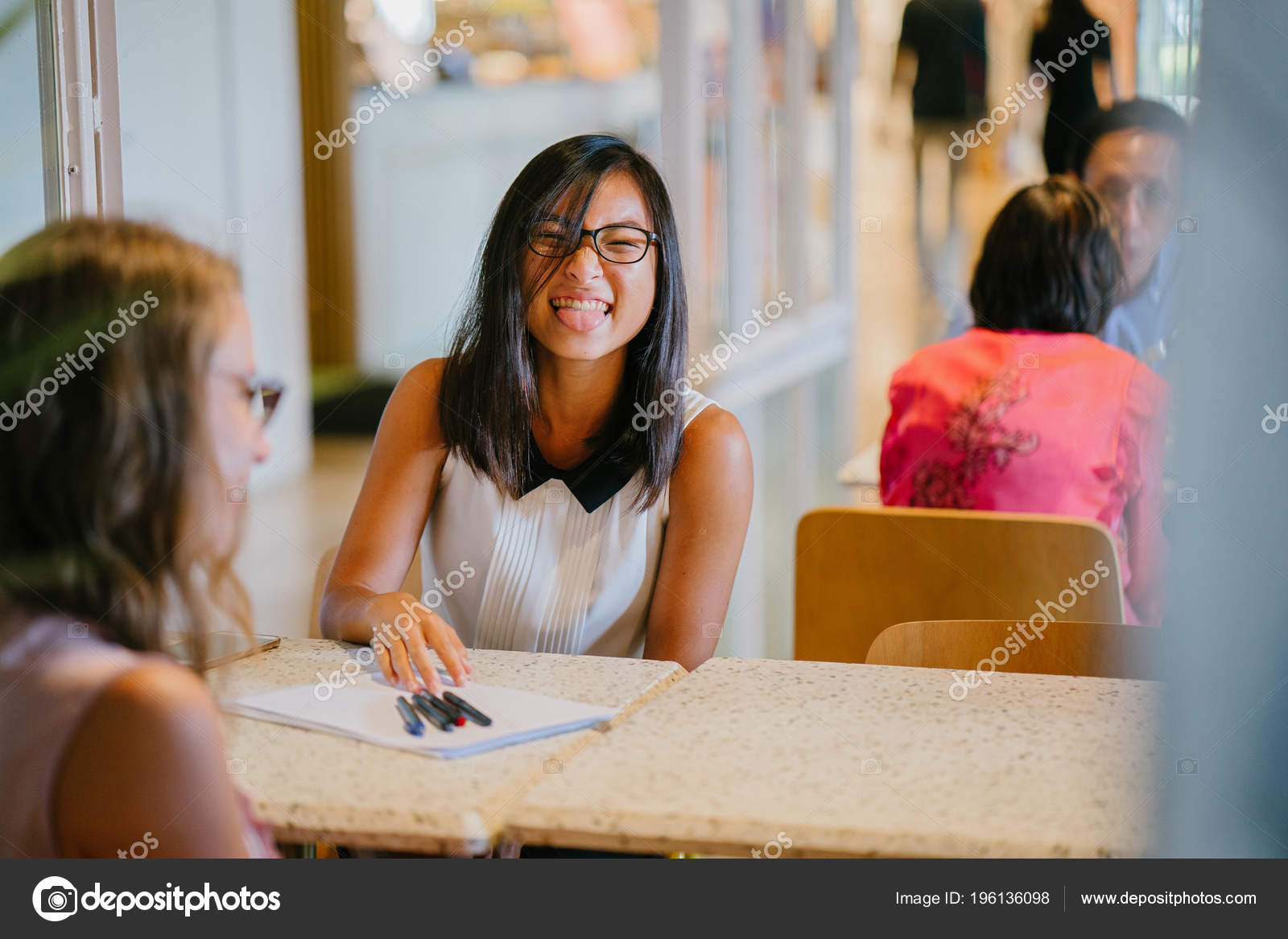 Two women colleagues have a business discussion in an office during the  day. One is a Chinese Asian woman and the other a Caucasian White woman.