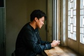 portrait of thoughtful man sitting with smartphone at wooden table near window