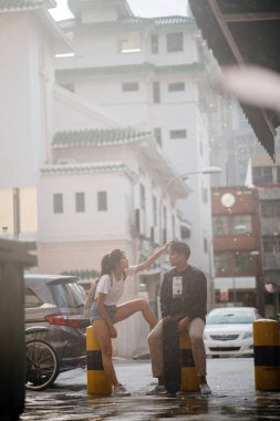 happy young couple talking on city street with cars on background, full length