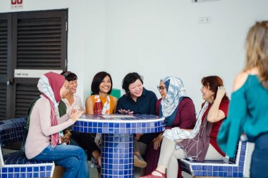 asian women laughing and talking sitting together at table