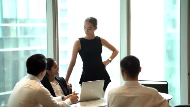 business people discussing projects sitting in modern office, businesswoman standing and speaking, making presentation