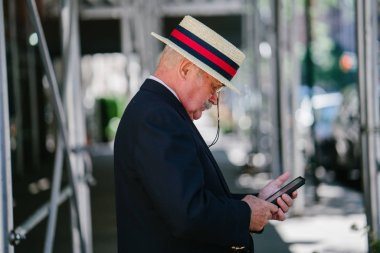Senior businessman wearing suit and using smartphone in city