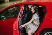Gyönyörű fiatal ázsiai nő, kisétált a piros autó