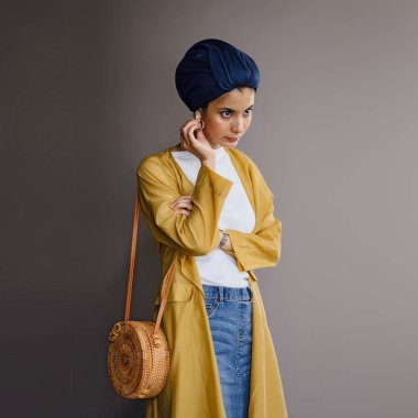 Fashion portrait of a tall, slim, young and attractive Malay Muslim woman wearing fashionable clothing and a turban