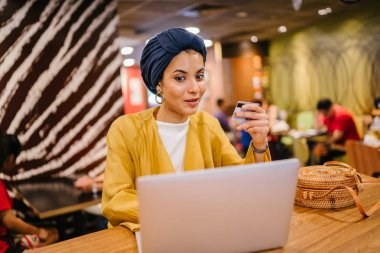 Portrait of a young and attractive Malay Muslim woman wearing a turban (hijab, head scarf). She is holding her credit card and keying in details to buy something online.