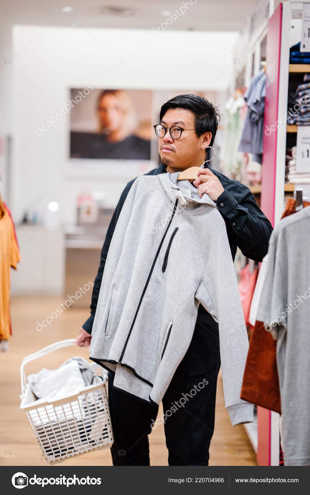 505a5d52b5fe Egy középkorú kínai férfi a vásárlás ruházati egy gyors divat áruház– stock  kép