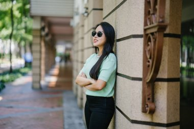 Portrait of a young, sexy and glamorous Asian woman leaning against a stone wall during the day. She is wearing a mint green sweater to match her black pants