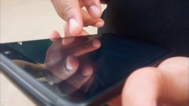 Nahaufnahme eines Mannes, der mit dem Finger auf einem schwarzen Tablet wischt. Afrika-Mensch. Black.Diversity.Hands hält ein smartphone.Working.Touch-Screen ist bei schwachem Licht eingestellt. Irgendwann öffnet er eine Schachpartie, die für ihn sichtbarer ist als die Kamera. Kühl.