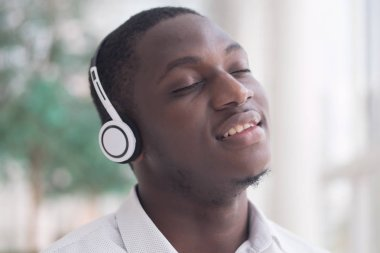 Modern African man listening to music headsets; portrait of happy smiling Black African man enjoying digital mobile music player device; African man young adult model