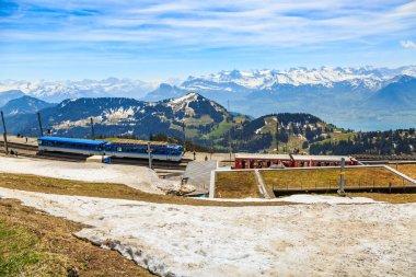 RIGI, SWITZERLAND - 25 APRIL 2018 - Rigi Kulm railway station on peak of Mount Rigi with blue cogwheel train is on standby to Arth-Goldau and red one to Vitznau