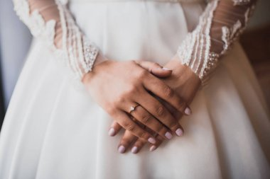 The female hands of the fair-skinned bride lie on the white wedding dress