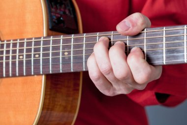 Fingers of a guitar player playing acoustic guitar.