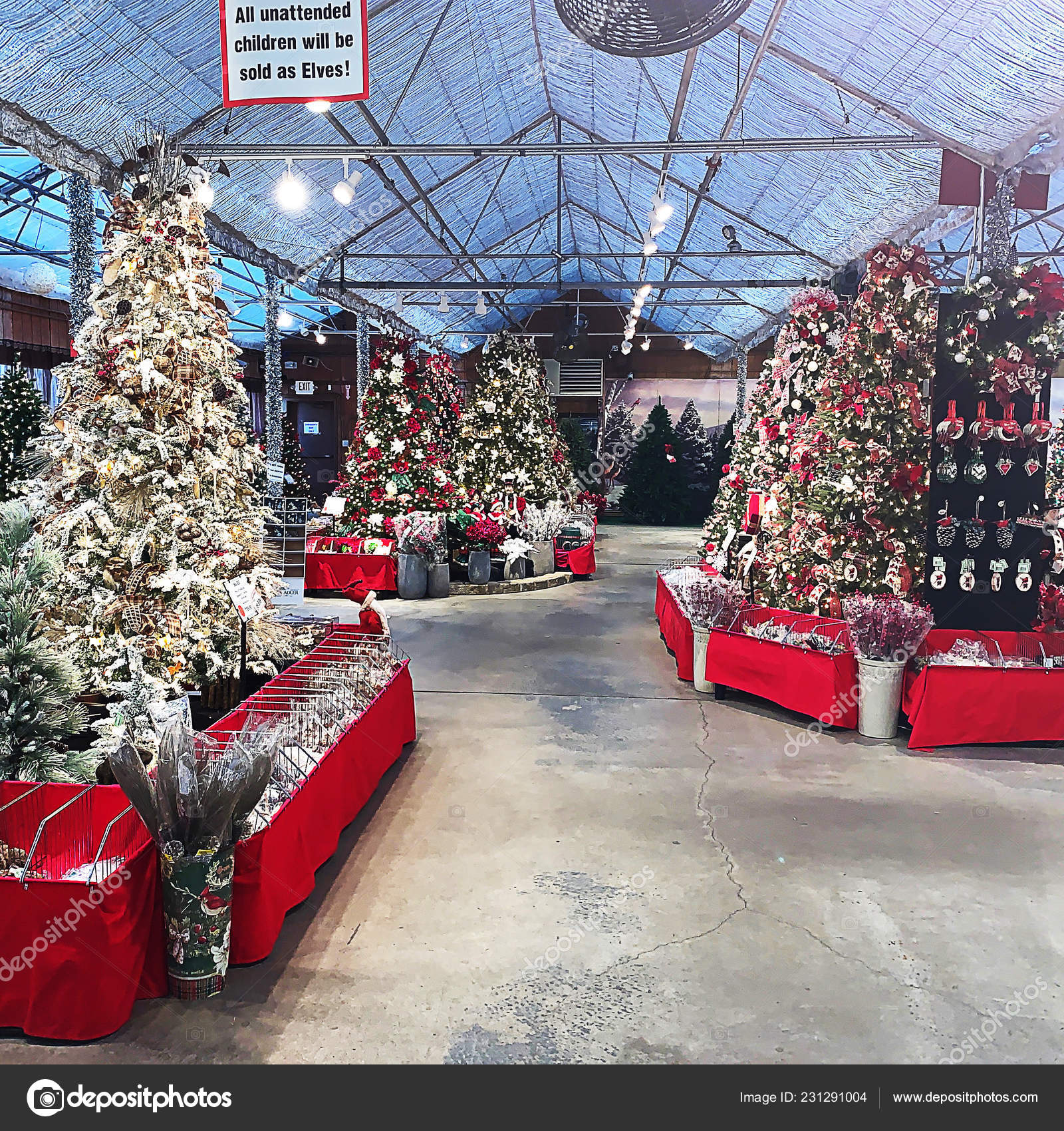 Beautifully decorated Christmas trees in large warehouse facility with ornaments below in containers for sale to the public at a local market.