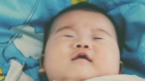 Close up face of a two-month adorable asian baby relaxing. Newborn baby yawning and lying on the bed. Healthy children concept. Vintage film filter effect. Cinematic style colors.