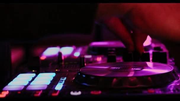Közelkép a kezében egy Dj játszik a digitális vezérlő egy sötét szórakozóhelyen környezetben