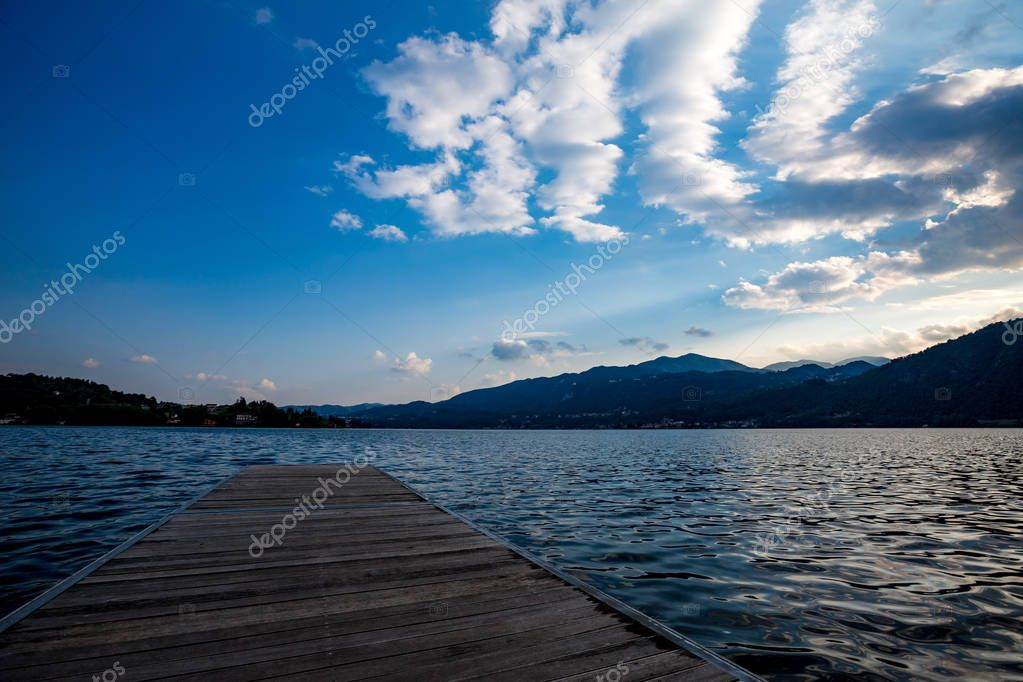 Simple wooden quay in Italy, Lago di Maggiore, leading into the calm blue waters of the lake in the evening