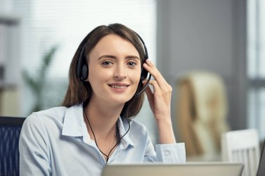 Young beautiful brunette woman working as call operator in telemarketing center and speaking with client in headset