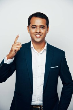 Portrait of smiling Indian businessman in suit raising index finger up and looking at camera