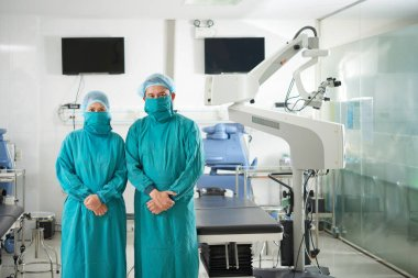Asian doctors in green coats and masks standing in operation room