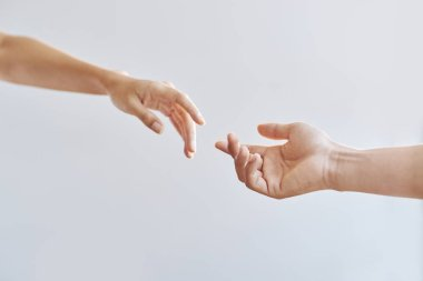 cropped image of man and woman hands stretching to each other