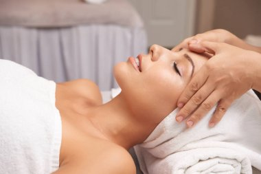 Calm female taking pleasure in relaxing massage on her face in spa salon