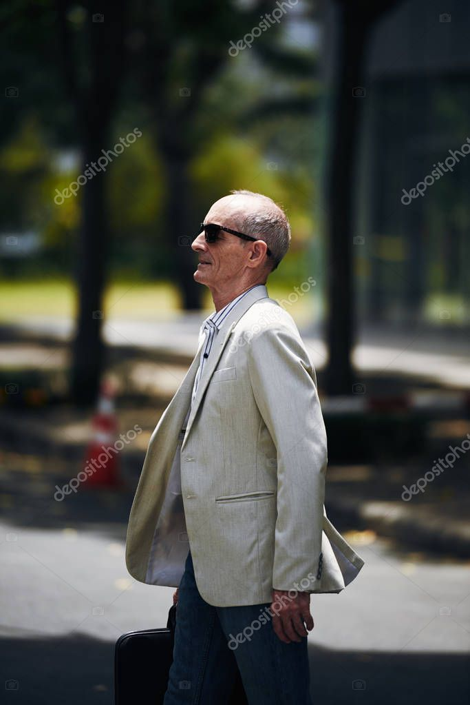 Aged entrepreneur in sunglasses walking in the street