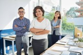 Cheerful Vietnamese business lady and her coworkers in office