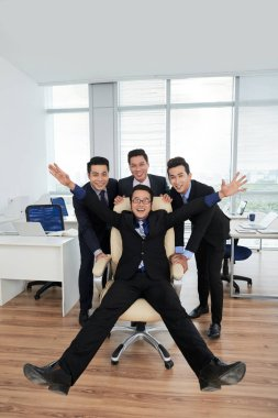 Group of smiling Asian managers pushing chair with colleague