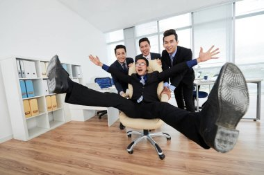 cheerful Asian managers having fun in office