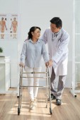 Photo asian doctor helping senior patient to use front-wheeled walker