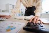 Business Lady berechnet Umsatz für Finanzbericht, selektive Fokussierung